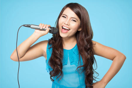 beautiful stylish woman singing karaoke isolated over blue background