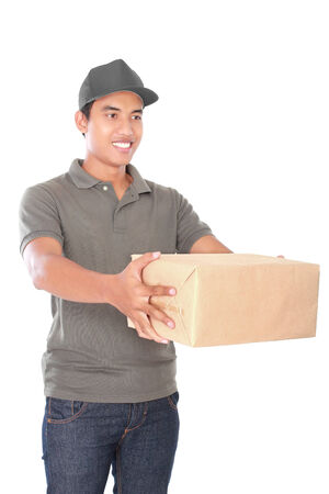 stretch out: portrait of happy man courier in grey uniform stretch out his arm delivering packages isolated on white background