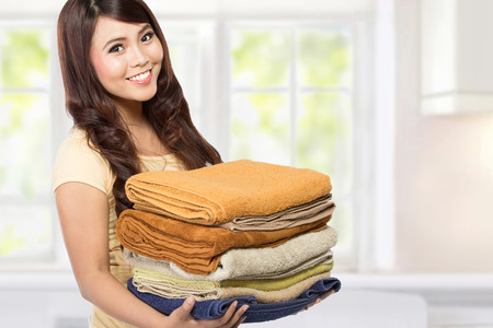 household tasks: woman doing a housework holding laundry at home Stock Photo