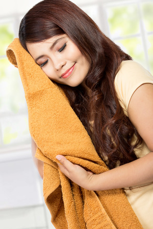 houseclean: young woman holding and smelling the fresh clean laundry