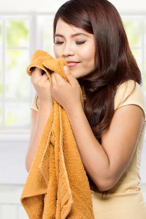 lavando ropa: mujer joven sosteniendo y oliendo la ropa fresca y limpia Foto de archivo