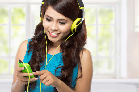 teenage girl: young asian girl listening music with headphones