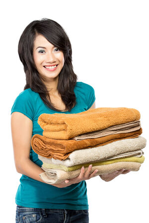 household tasks: woman doing a housework holding laundry isolated over white background Stock Photo