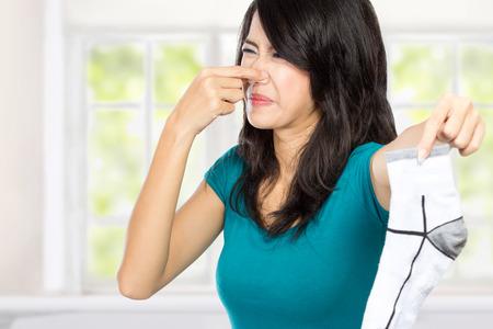 mujer joven que sostiene y oler la ropa sucia