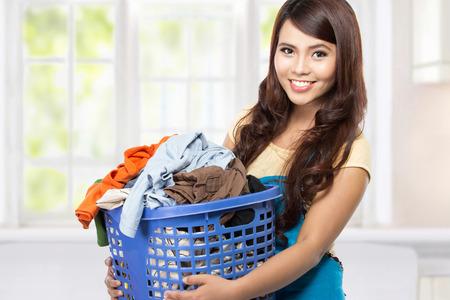 housekeeper: mujer haciendo una lavander�a tareas dom�sticas sosteniendo Foto de archivo