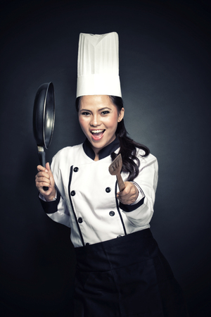 portrait of excited female chef or baker ready to cook photo