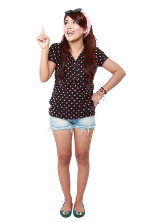 woman pointing up: Portrait of attractive young woman pointing up over white background