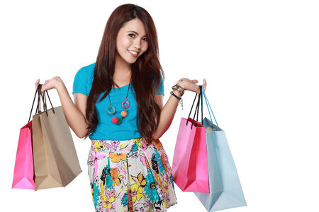 asian girl shopping: happy shopping girl holding shoping bags in hands. over white background