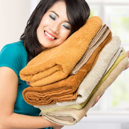 woman doing a housework holding laundry. smell good