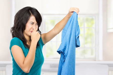 houseclean: young woman holding and showing dirty clothes Stock Photo