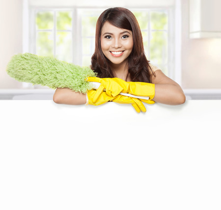 Domestic cleaning: Cleaning service woman presenting a blank board and hold a duster