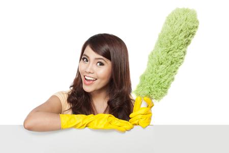 Servicio de limpieza de la mujer que presenta una tarjeta en blanco y mantenga un plumero