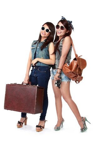 woman bag: portrait of Happy two girls going on vacation walking with suitcase and smile Stock Photo