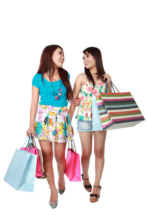 asian girl shopping: happy two shopping girl friend holding bags and walking. isolated in white background