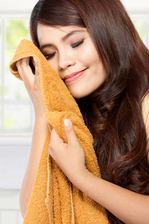 mujer joven sosteniendo y oliendo la ropa fresca y limpia