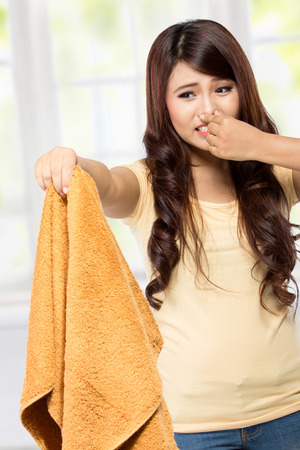 bad hygiene: portrait of housewife holding a bad smell laundry