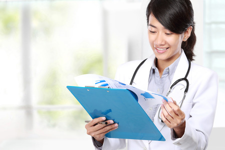 asian nurse: portrait of Happy smiling female doctor reading a report