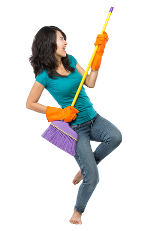 household work: Cleaning girl happy excited during cleaning. Funny girl with cleaning mop playing guitar isolated on white background