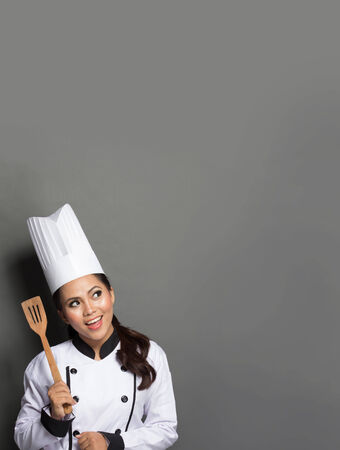 cook house: female chef with spatula and thinking what to cook
