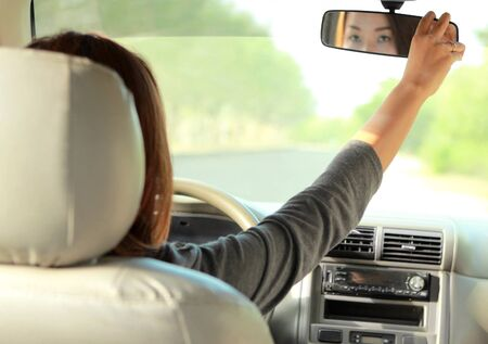 rearview: portrait of a woman driving a car while adjusting rearview mirror