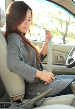 hand brake: side view of young woman putting on a safety belt in the car Stock Photo
