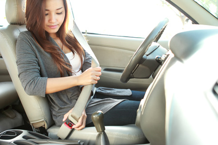 cars on the road: portrait of young woman putting on a seatbelt for safety Stock Photo