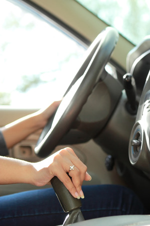 clutch: portrait of woman driving and shifting car transmission with both hands