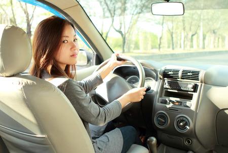 아름다운 젊은 여자가 차를 몰고 다시의 설정 할 수있는 방법을 찾고
