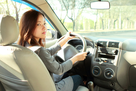 beautiful young woman driving a car and looking a way to turn back of photo