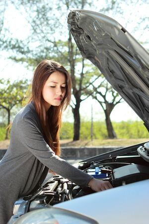 car trouble: portrait of young woman get into engine problem on the way