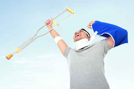 crutch: portrait of cheerful injured young man hold up the crutch