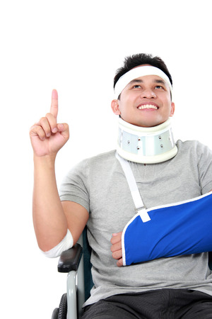 portrait of cheerful young men with broken arm pointing upwards Stock Photo