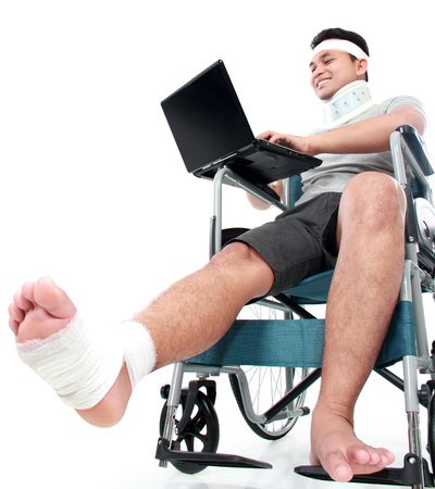 taken: portrait of young man with broken leg in wheelchair work on his laptop