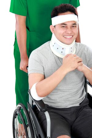 portrait of injured young man in wheelchair help by nurse photo