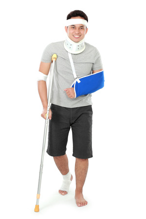 full length portrait of  injured young man on crutch photo