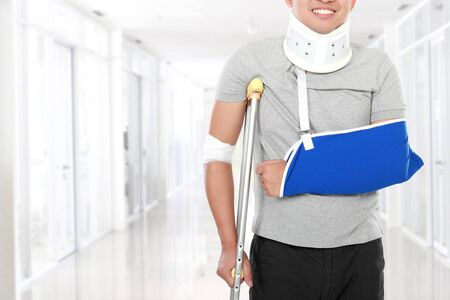 crutch: portrait of injured young man use crutch and arm sling Stock Photo