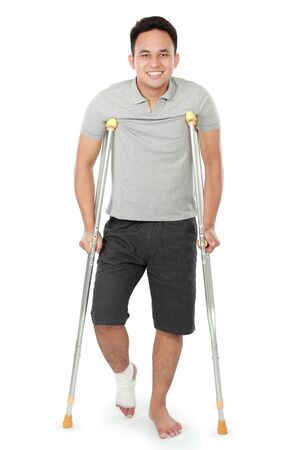 crutch: full length portrait of young man with broken leg use crutches
