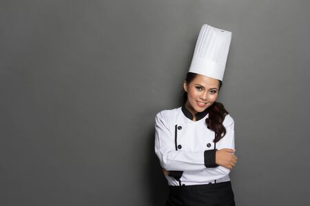 cook house: portrait of young female chef crossed arm against gray background