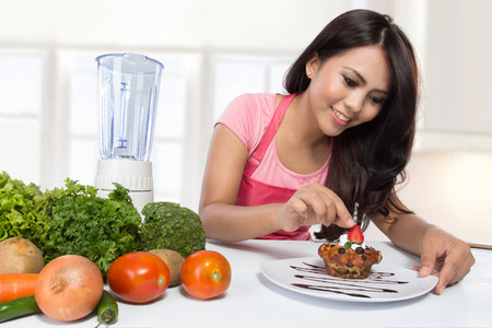 asian cook: portrait of Cooking woman in kitchen garnishing some food Stock Photo