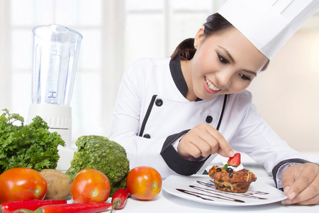 chef uniform: beautiful asian female chef garnishing in the kitchen