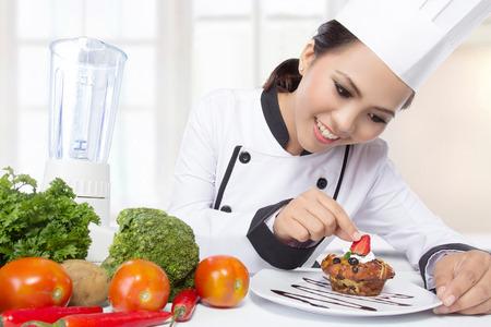 mooie Aziatische vrouwelijke chef-kok garnering in de keuken