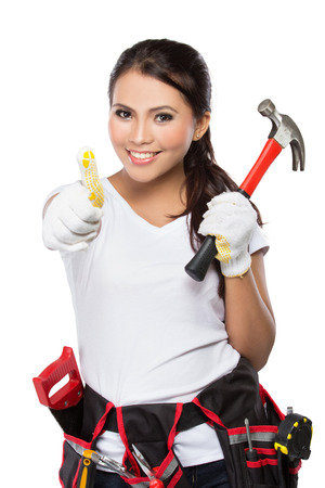 portrait of young asian woman with hammer showing thumb up isolated over white background photo