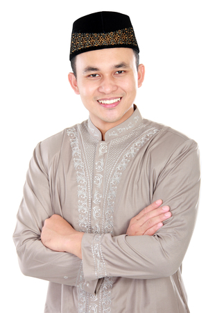 portrait of handsome muslim man smiling with arm crossed on white background photo