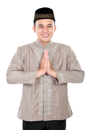 spiritually: portrait of cheerful young muslim man on white background