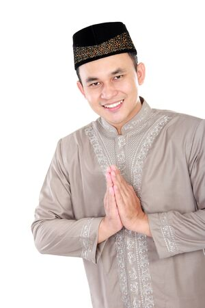 spiritually: portrait of young muslim man smiling and posing on white background