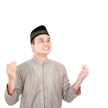 portrait of young muslim man praying with white background