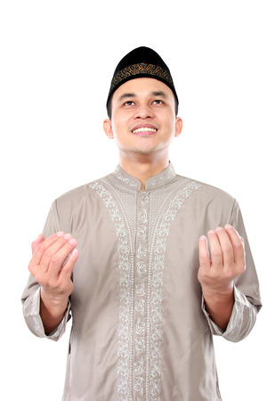 front view portrait of young muslim man looking upward and praying to God photo
