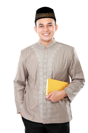 spiritually: portrait of handsome young muslim carrying the Quran on white background