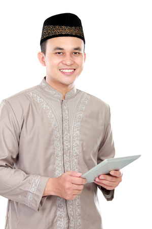 spiritually: handsome young muslim man holding a tablet on white background