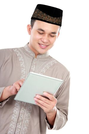 skull cap: portrait of young muslim man enjoy playing on his tablet on white background